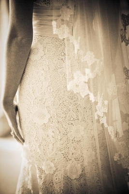 Sepia tone image of spring wedding lace bridal gown skirt details