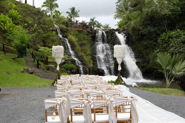 Outdoor Hawaiian wedding ceremony facing a waterfall