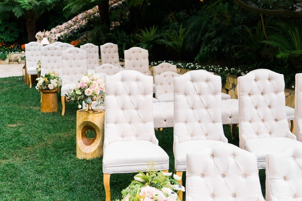 Grey tufted chairs for ceremony with wood side tables flowers in vase green lawn grass