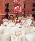 White table and slip-covered chairs with pink centerpiece