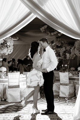 Black and white photo of bride popping foot as she kisses groom