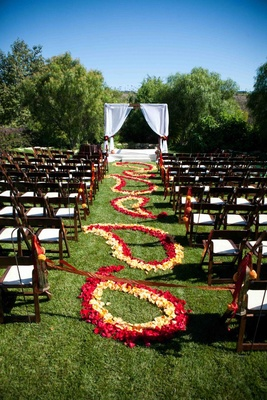 Outdoor wedding aisle decorated with a red and yellow paisley pattern