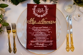 Gold flatware next to charger plate with burgundy menu napkin and laser cut name tag