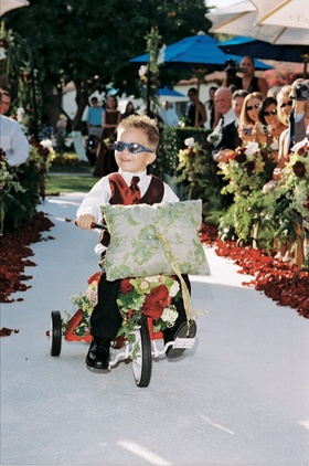 Young boy wearing red vest on flower embellished red tricycle