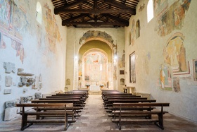 wedding ceremony historic abbey eighth century fresco paintings on walls wood pews altar wood beams