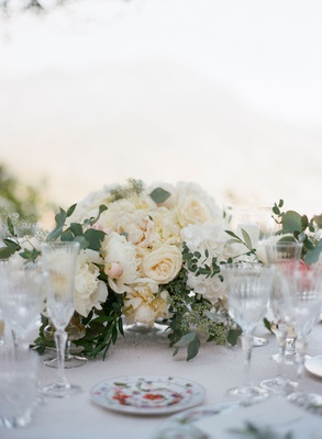 Wedding reception low centerpiece ivory rose white peony hydrangea greenery colorful china