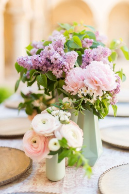 wedding reception small centerpiece pink ranunculus flowers purple flowers greenery faceted vase
