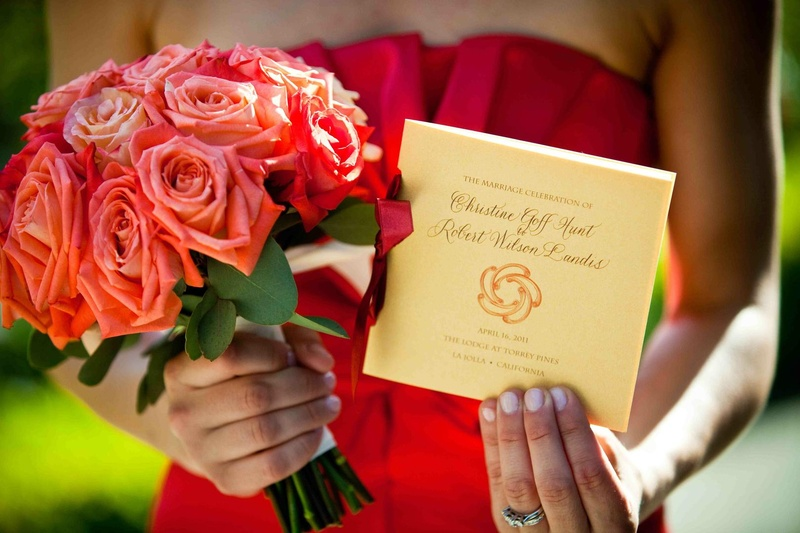 Red-orange rose bouquet and ceremony booklet