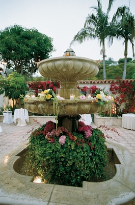 Stone fountain covered with greenery, flowers, and candles