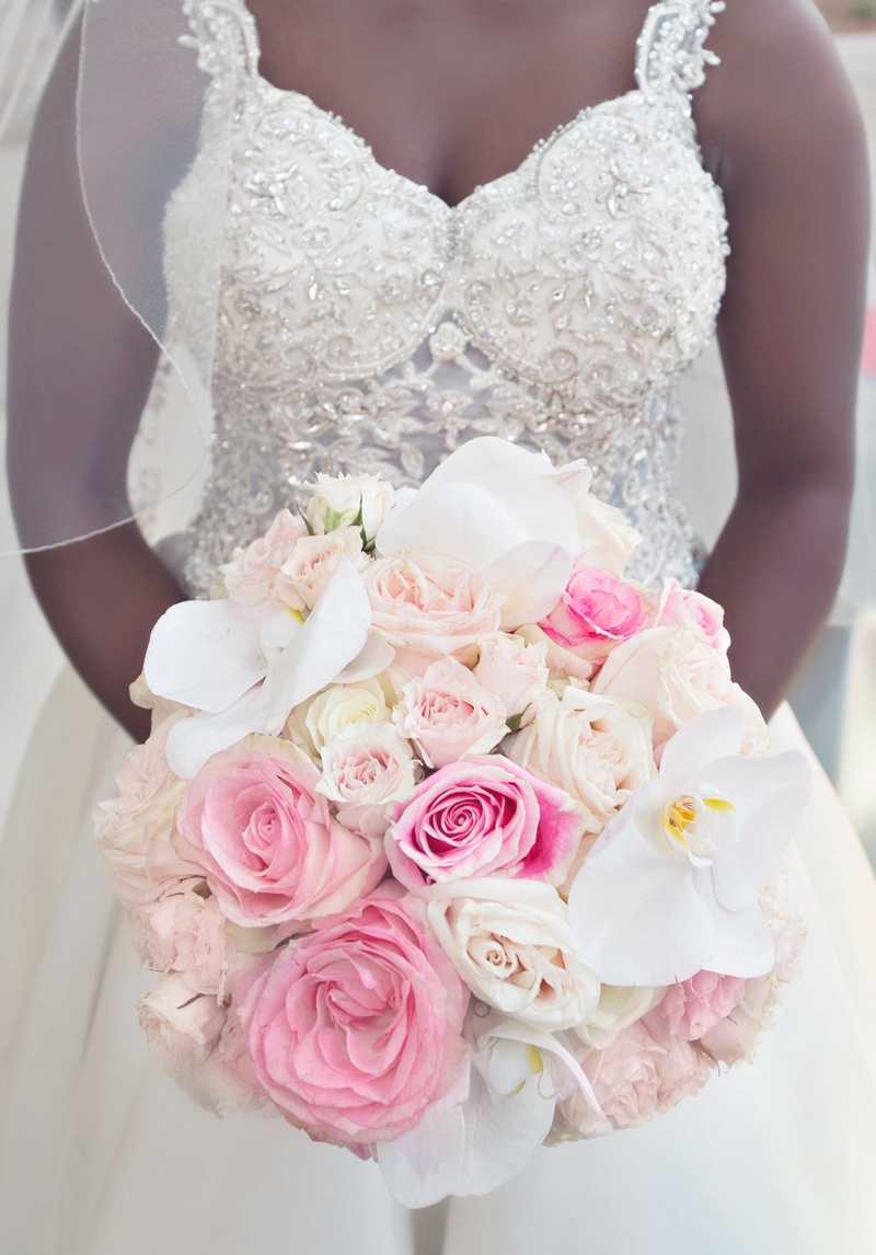 Bride in jewel bodice wedding dress holding pink rose white orchid bridal bouquet