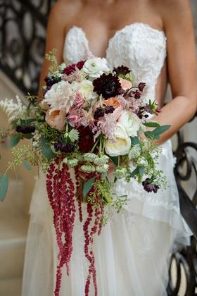 Bride holding fall bouquet burgundy amaranthus white flowers pink ranunculus rose eucalyptus