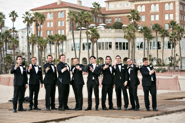 Groomsmen taking self portraits on their phones selfie photo on beach boardwalk in Santa Monic