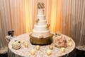 White textured wedding cake with light orange roses, couple's golden monogram