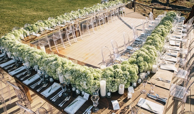 Rustic wood table topped with green hydrangea runner