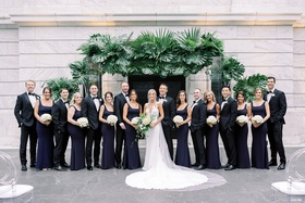 wedding party bride groom bridesmaids and groomsmen in front of ceremony arch tropical greenery