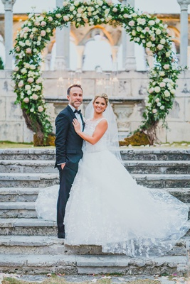 bride in lace a-line isabelle armstrong gown with groom in front of circular ceremony arch