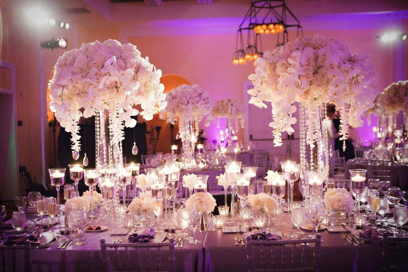 Tall white centerpieces with floating candles and purple lighting