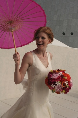 Bride on wedding day holding umbrella and nosegay