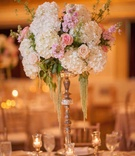 Wedding reception table with high gilded stand, white hydrangeas, pink and peach roses, amaranthus