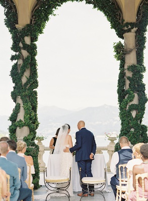 bride and groom lake como wedding ceremony greenery on stone pillar archway villa del balbianello
