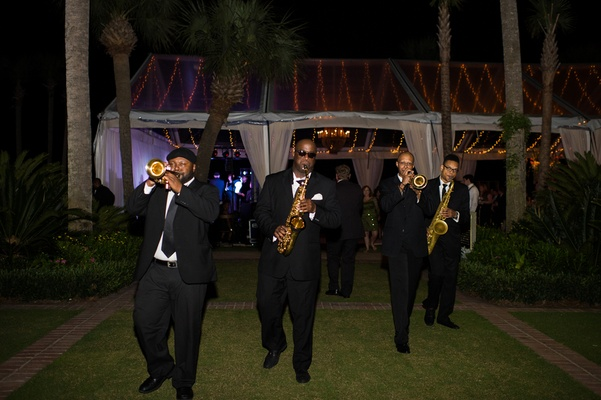 Men in tuxedos playing the saxophone outside