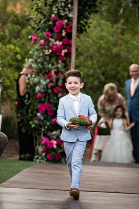 cute ring bearer in light blue suit white bow tie moss ring pillow wood aisle pink flowers
