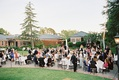 Outdoor wedding at bride's parents' house with round tables and long farm tables
