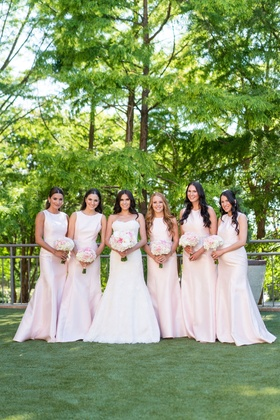 Bride in monique lhuillier wedding dress with bridesmaids in pink high neck floor length gowns