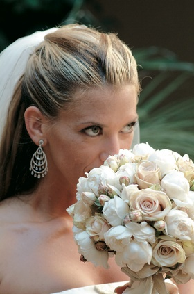 Bride wearing earring smells flower bouquet