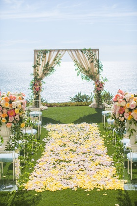 wedding ceremony aisle yellow flower petals arch with greenery ocean view laguna niguel