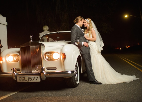 Groom in grey suit and bride in white dress on English luxury car