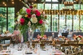 colorful wedding reception decor twinkle lights view of outside trees greenery wood chairs tables