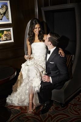 bride in oscar de la renta sitting on lap with groom in j. hilburn, champagne glasses