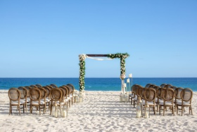 wedding ceremony on sand beach modern arch greenery pink flower gold lantern cane round chair back