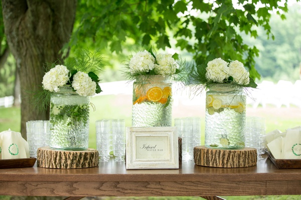 Wood table with wood stump riser infused water bar lemon lime orange hydrangea decorations