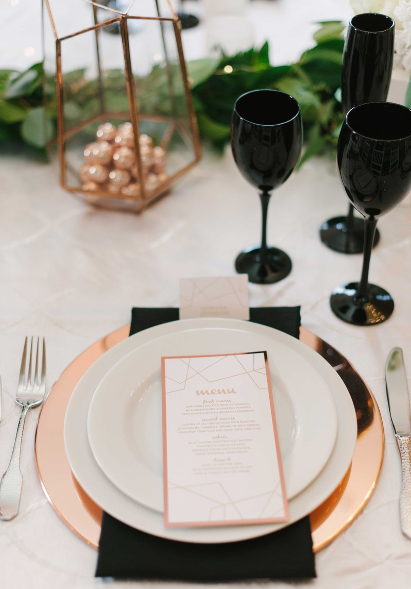 a tablescape featuring black white and copper accents in chargers glasses linens and green runner