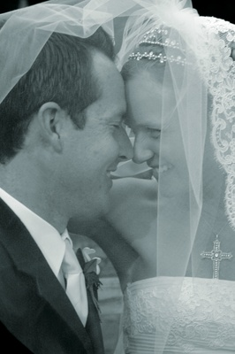 Black and white photo of couple under veil