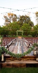 raised platform jewish wedding ceremony greenery small candles lanterns alfresco