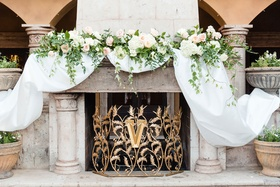 Custom gold cover with initial monogram white drapery and blush ivory flowers greenery on mantel