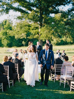 Bride and groom walking down the aisle cape over wedding dress holding groom hand blue suit
