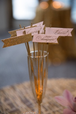 Glittery gold and blush drink stirrers in glittery gilt champagne flute