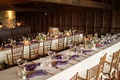 Long king's tables at winery vineyard wedding reception indoor dinner wood chairs purple napkins