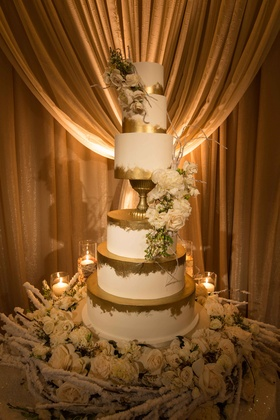 Six layer white wedding cake with gold paintbruch stroke accents on winter cake table