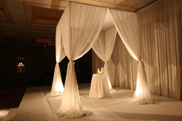 Chuppah constructed of sheer white fabric