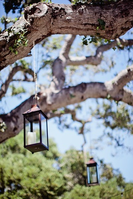Rectangular lantern suspended from tree by twine