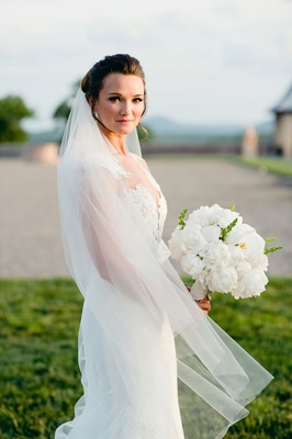 Bride in lace wedding dress illusion neckline in veil with white peony flower bouquet orchid
