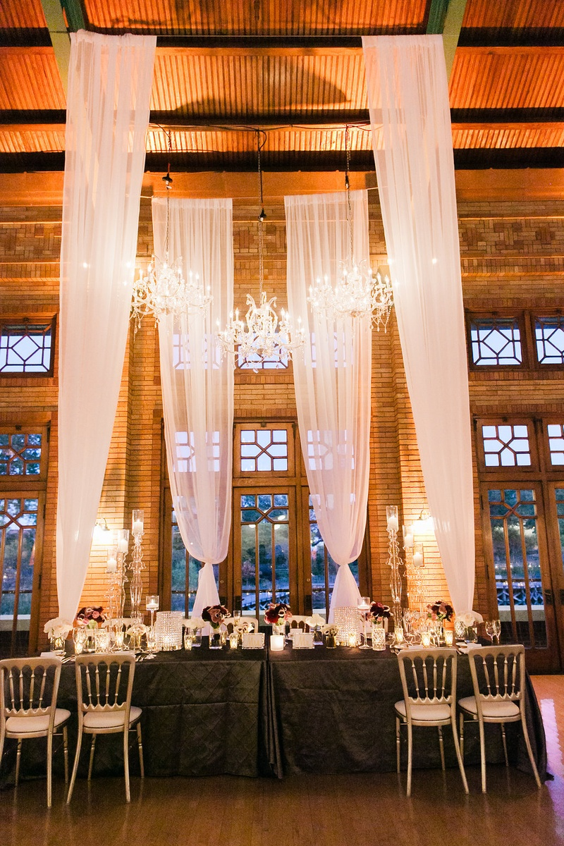 Wedding reception table with tall drapery canopy chandeliers purple flowers low centerpieces