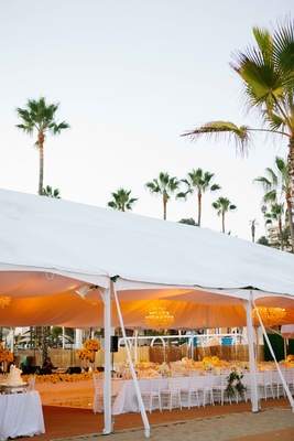 Beach tented reception with amber lighting, crystal chandeliers, white linens, flowers, chairs