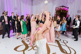 bride looks back as women jump for bouquet during wedding reception