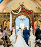 Bride and groom at gold altar white and red sash white flowers